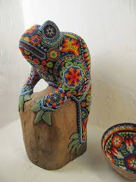 Wooden sculture adorned by a Huichol Indian with beads in the traditional pattern and vibrant colors.