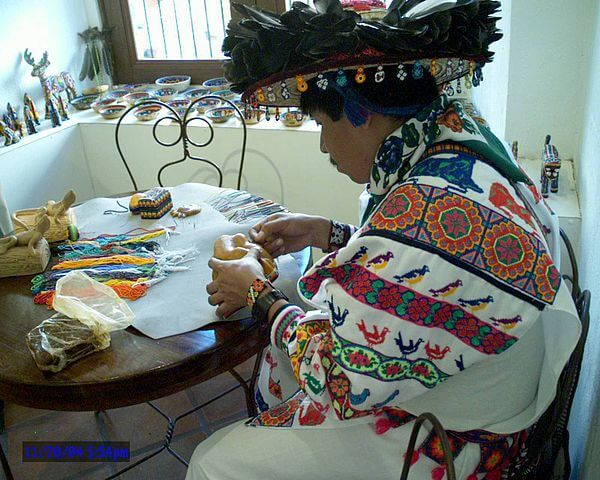 A Huichol Indian and artisan creating another piece of art.
